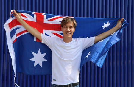 The man in white shirt is holding Australia flag in his hands and raising to the end of the arm at the back on blue background.