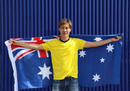 The man in yellow shirt is holding Australia flag on his shoulder on blue background. Archivio Fotografico