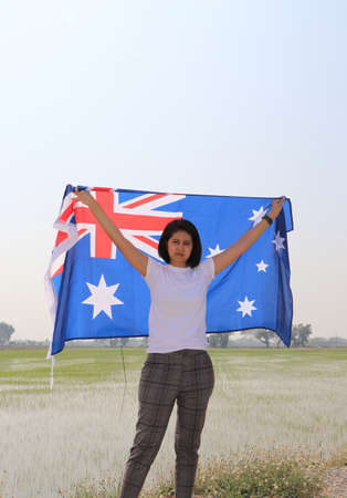 pretty lady is holding Australia flag in her hands and raising to the end of the arm at the back on nature view and rice fields background.