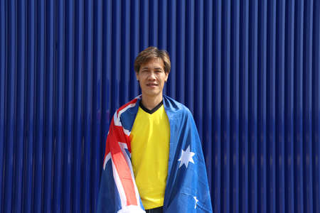 The man in yellow shirt with Australia flag on his shoulder on blue background. Archivio Fotografico