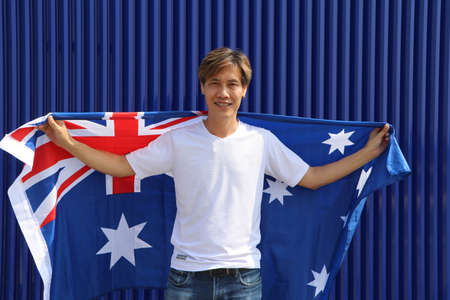 The man in white shirt is holding Australia flag on his shoulder on blue background. Archivio Fotografico