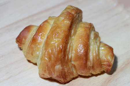 The croissant is placed on the wooden floor. It is a French crescent shaped roll made of sweet flaky pastry, often eaten for breakfast.
