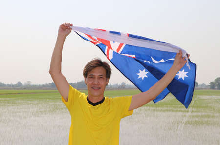 The man in yellow shirt is holding Australia flag in his hands and raising to the end of the arm at the back on nature view and rice fields background. Archivio Fotografico