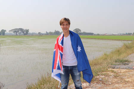 The man in white shirt with Australia flag on his shoulder on nature view and rice fields background. Archivio Fotografico