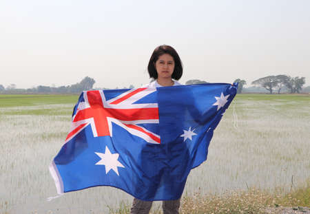 pretty lady is holding Australia fabric flag in her hands nature view and rice fields background.