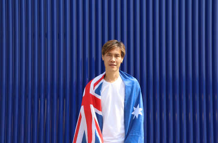 The man in white shirt with Australia flag on his shoulder on blue background.