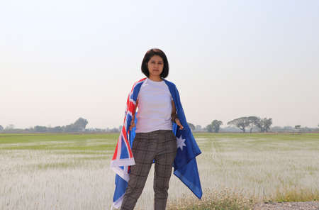pretty lady in white shirt with Australia flag on her shoulder on nature view and rice fields background.
