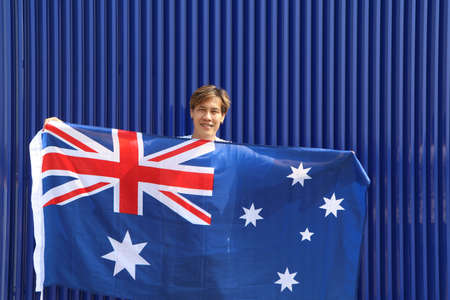 The man is holding Australia fabric flag in his hands on blue background.