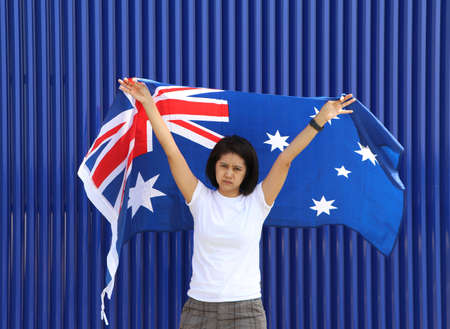 pretty lady is holding Australia flag in her hands and raising to the end of the arm at the back on blue background.