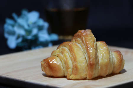 The croissant placed on the square wooden tray with out focus tea in a glass and blue flowers on dark background. It is a French crescent shaped roll made of sweet flaky pastry, often eaten for breakfast.