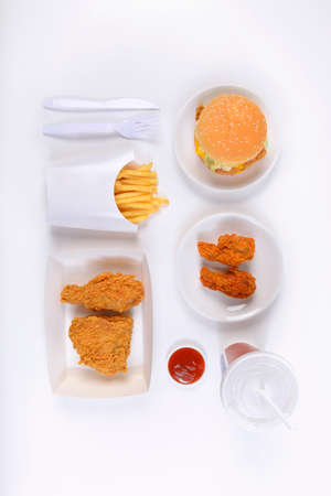 Fast food set containing burgers, fried chicken, french fries and soft drink isolated on white background.