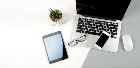 Office table with laptop computer, digital tablet and mobile phone on modern two tone (white and grey) background.