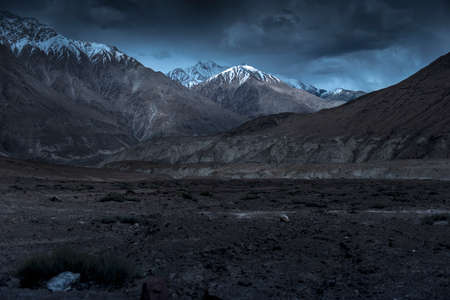 Beautiful landscape snow mountains at night on blue cloud background. Leh, Ladakh, India.