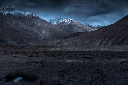 Beautiful landscape snow mountains at night on blue cloud background. Leh, Ladakh, India.