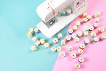 Sewing machine and colorful thread rolls for sewing on two tone background, Sewing and needlework concept.