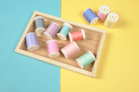 Flat lay of colored thread rolls for sewing on two tone background, Sewing and needlework concept.