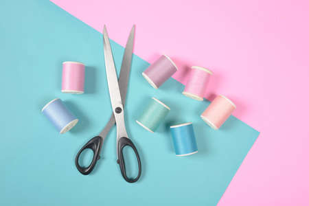 Flat lay of colored thread rolls and Scissors for sewing on two tone background, Sewing and needlework concept.