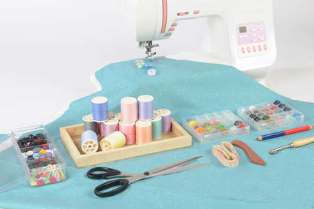 Sewing machine and colorful thread rolls, scissors, fabric and accessories for sewing on white background, Sewing and needlework concept. (Selective Focus) Standard-Bild