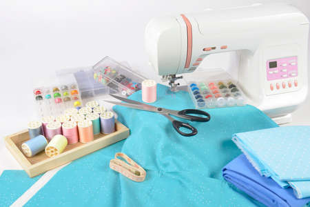 Sewing machine and colorful thread rolls, scissors, fabric and accessories for sewing on white background, Sewing and needlework concept. (Selective Focus) Archivio Fotografico
