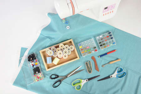 Sewing machine and colorful thread rolls, scissors, fabric and accessories for sewing on white background, Sewing and needlework concept. (Selective Focus) Foto de archivo