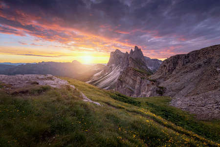 Amazing landscapes view of green mountain with gold sky on sunrise morning from Dolomites, Italy. 免版税图像