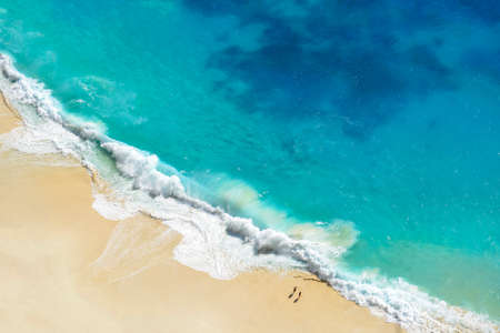 Aerial view of seascape blue ocean wave on sandy beach background.