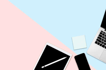 Flat lay photo of office table with digital tablet, mobile phone and accessories. on modern two tone (blue and pink) background. Desktop office mockup concept.