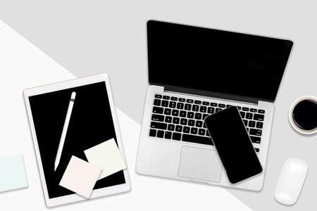 Table de bureau à plat avec ordinateur portable, tablette numérique, téléphone portable et accessoires sur fond bicolore blanc et gris. Concept de maquette de bureau de bureau.