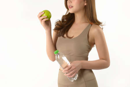 Pretty asian woman with apple and water on white background.