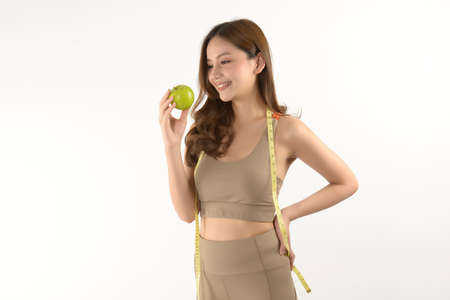 Pretty asian woman with apple and measure tape on white background.