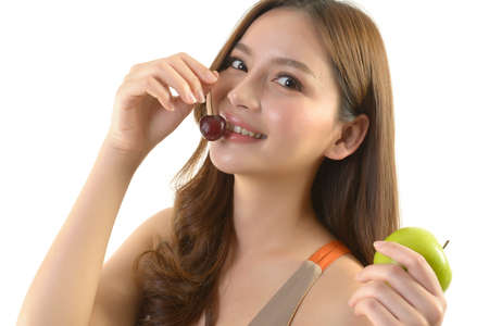 Pretty asian woman with apple and cherry on white background.