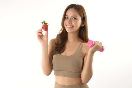Pretty asian woman with dumbbell and strawberry on white background.
