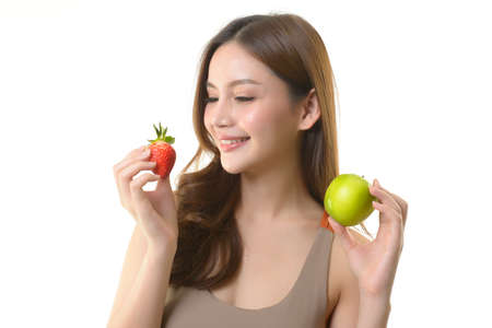 Pretty asian woman with apple and strawberry on white background.