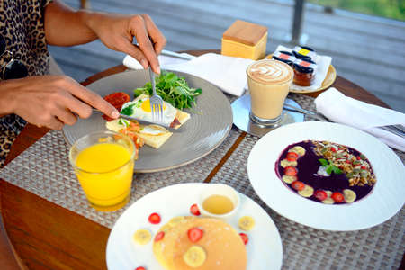 Breakfast served with fried egg, coffee, orange juice, cereals and fruits for healthy. Imagens