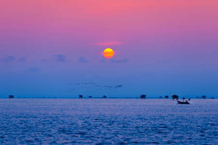 Fisherman and floating village in the ocean on sunrise.