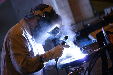 welding metal: Arc welder at work at his workbench Stock Photo