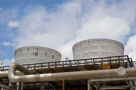 emitting: Two cooling towers emitting steam, with a blue sky background Stock Photo