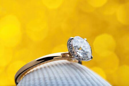 Diamond Ring on Seashell With Yellw Light Bokeh Background