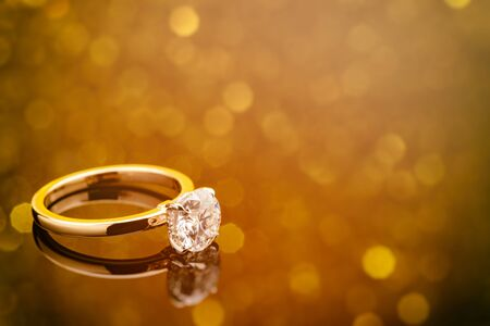 Engagement Diamond Ring on Golden Bokeh Background