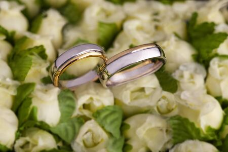 Wedding Rings on a Rose Bouquet Stock Photo