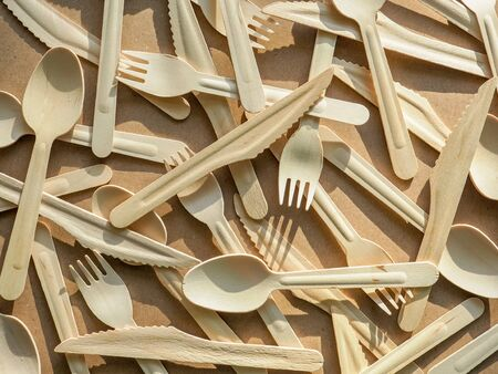 Ecology, zero waste concept. Eco friendly disposable kitchenware utensils on craft paper background. Wooden forks, knives and spoons. top view. flat lay.