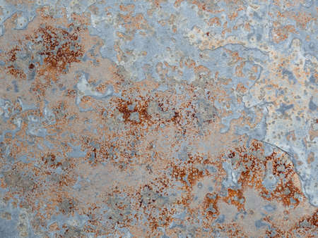 Corroded background. Texture of wall with brass and aqua patina. Blue silver surface with streaks of rust. Rusty corrosion. Brown, grey, blue and orange rust on enamel.