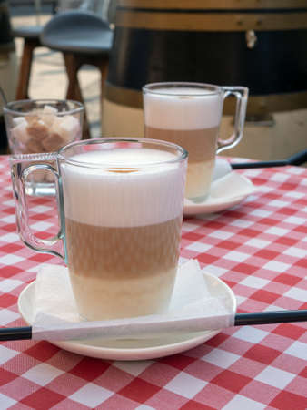 Cafe and bar, barista art concept. Frothy, layered cappuccino in a clear glass mug. Tempting coffee latte in two tall glasses in coffee house.