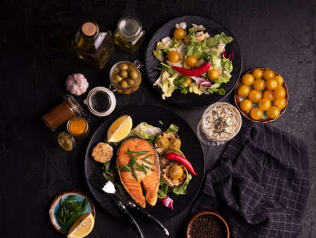 Healthy and diet food concept. Grilled salmon steak, salad with vegetables, olives and wine on black background. Top view, close-up. Red fish with garlic, yellow tomato and spices on black plate.