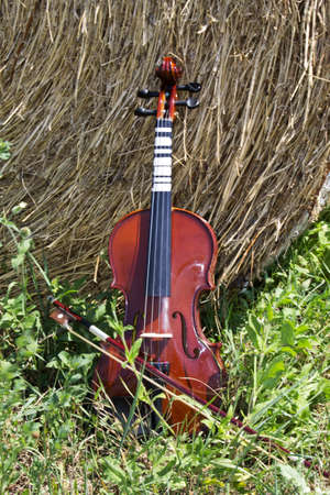Violin resting on a bale of hay Stock Photo