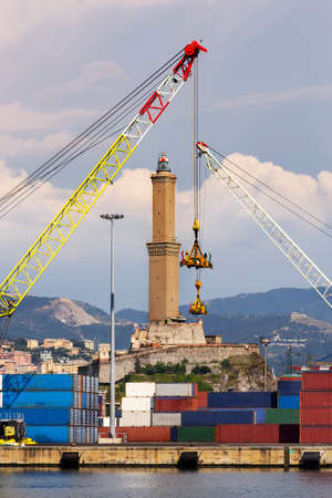 The lighthouse of Genoa between two cranes