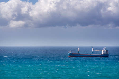 Container ship sails on the horizon