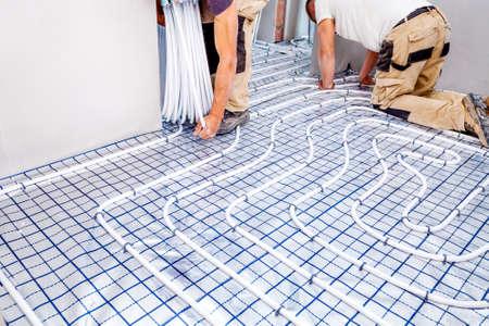 パイプフィッターは床暖房を取り付けた。暖房システムおよび床暖房。 写真素材