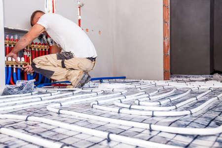 Rohrschlosser Fußbodenheizung montiert. Heizsystem und Fußbodenheizung. Standard-Bild