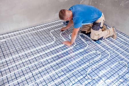 Pijp. fitter gemonteerde vloerverwarming. Verwarmingssysteem en vloerverwarming.